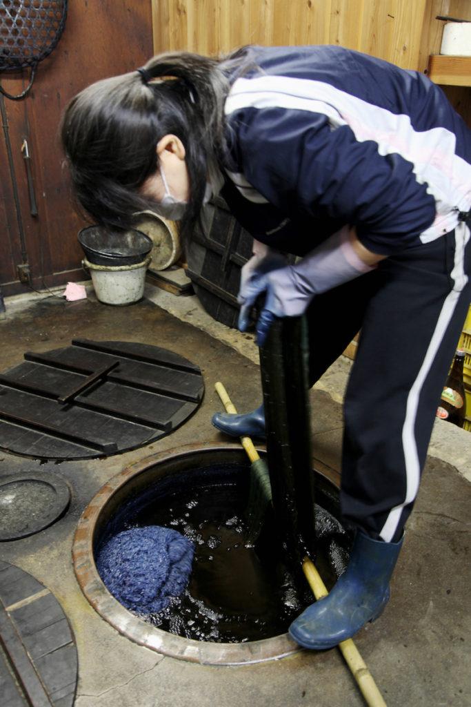 画像: 藍染の作業。地中に埋まったかめのなかで、本来は水に溶けない藍を発酵の過程で溶かし、染めを可能にする