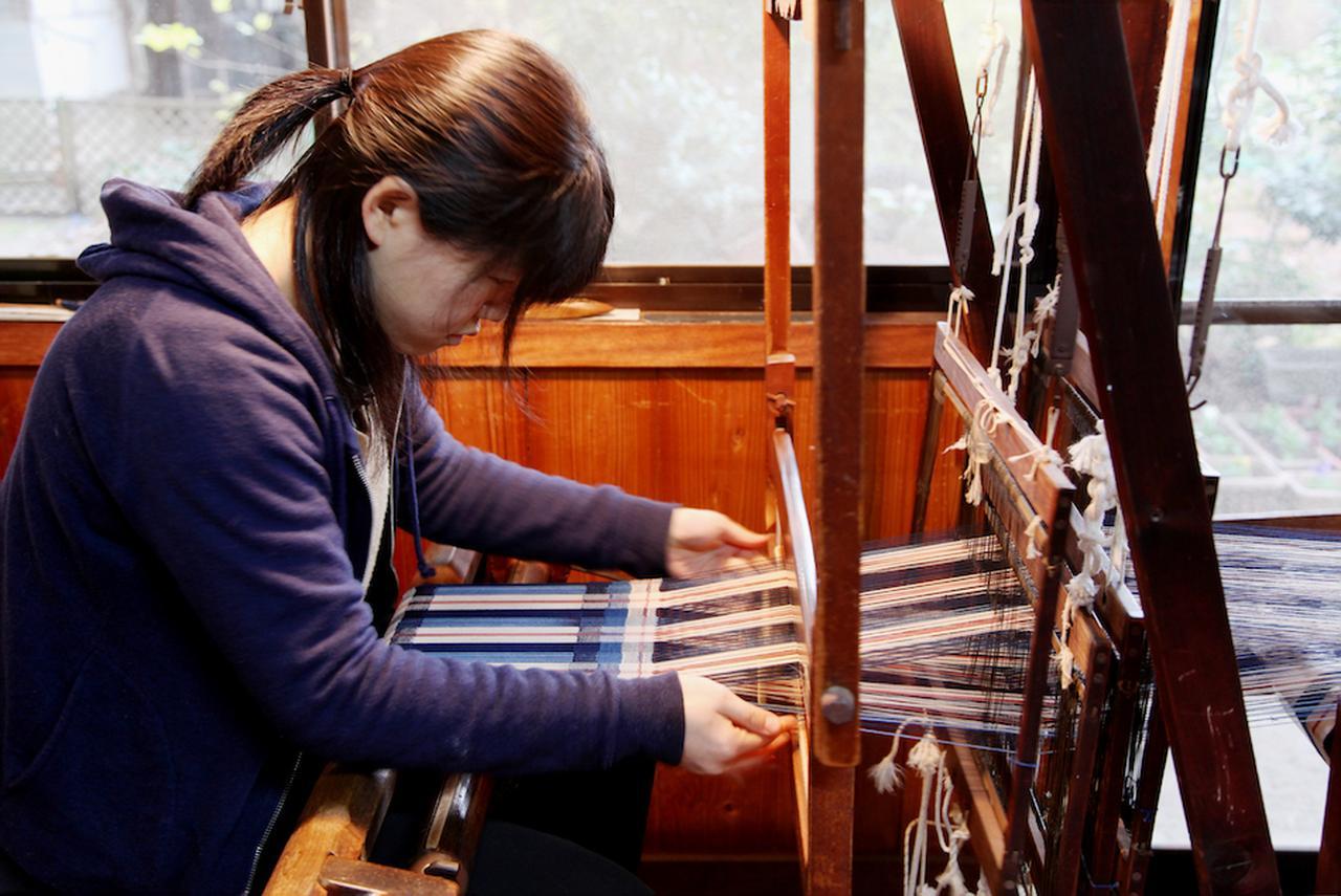 画像: 昔ながらの手織機で織っていく