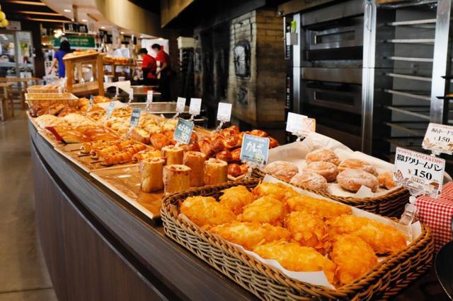 画像: 様々な種類の焼き立てパンが並ぶパン工房