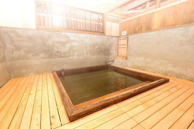 画像: 湯船がひとつあるだけの素朴な浴場。コンクリートを溶かす強酸泉であるため、湯船と床には松と桧が使用されている