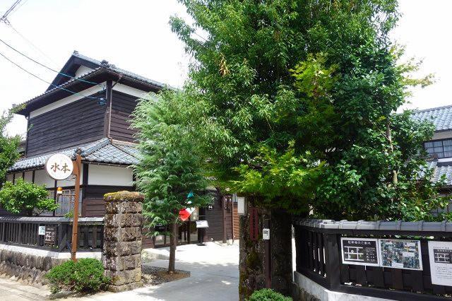 画像: 「水本学園高等女学校」と書かれた表札のある門を入る。左手の大正時代建築の木造建物の1階に店舗が