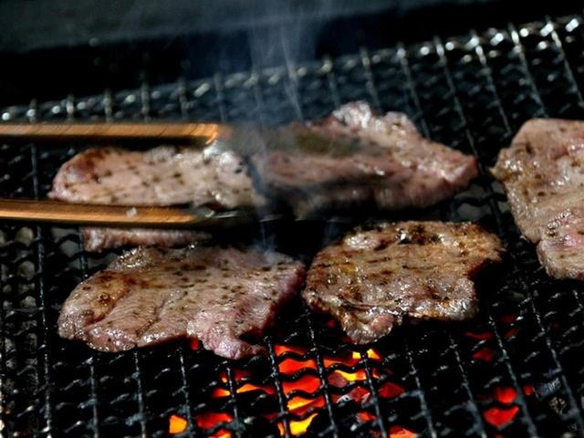 画像: メニューは「牛たんセット」のみ。オーダー後、牛たんを網に並べ、炭火で焼いていきます。