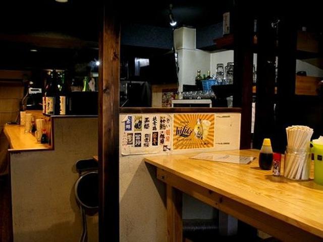 画像: 店内はカウンターと大きなテーブル席で構成されています。シックな照明で、隠れ家バー的な雰囲気もただよっています。