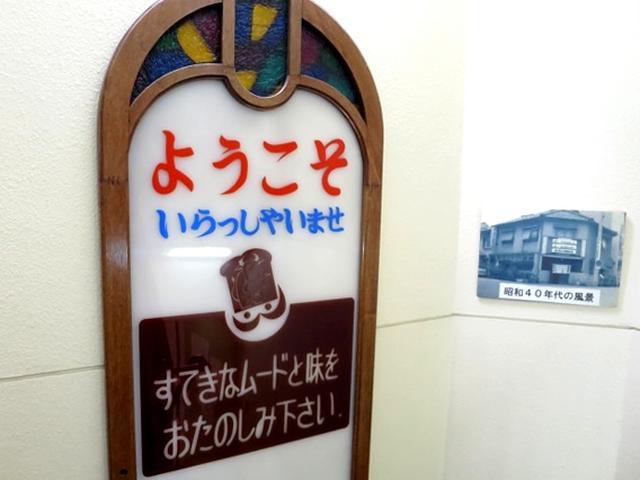 画像: 2階へと上がる階段の途中に昭和40年代の店舗風景の写真が飾られていました。