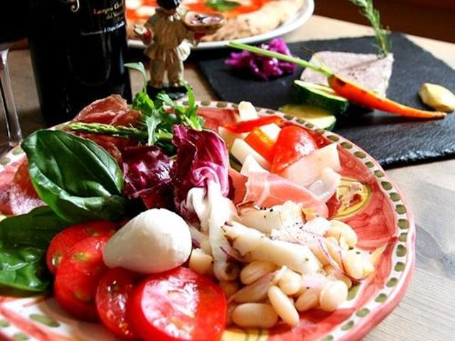 画像: 「本日の前菜盛り合わせ」や「田舎風 お肉のパテ」など、ピッツァ以外のメニューも充実。徳島の食材も数多く使われているそう。