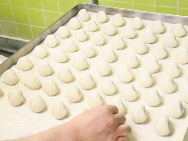 画像: 「温泉まんじゅう」は、店内で作られていきます。練り機から出てきたまんじゅうを、ひとつずつ手作業で並べていきます。