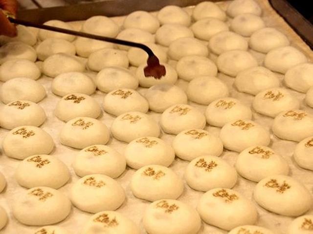 画像: 機械で蒸すこと数分。熱々のおまんじゅうに、焼きゴテでひとつずつ「箱根丸嶋」と描かれた刻印を押していきます。