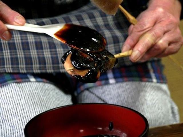 画像: この道数十年のベテランさんが、丁寧に一串ずつ自家製の田楽味噌を塗っていきます。