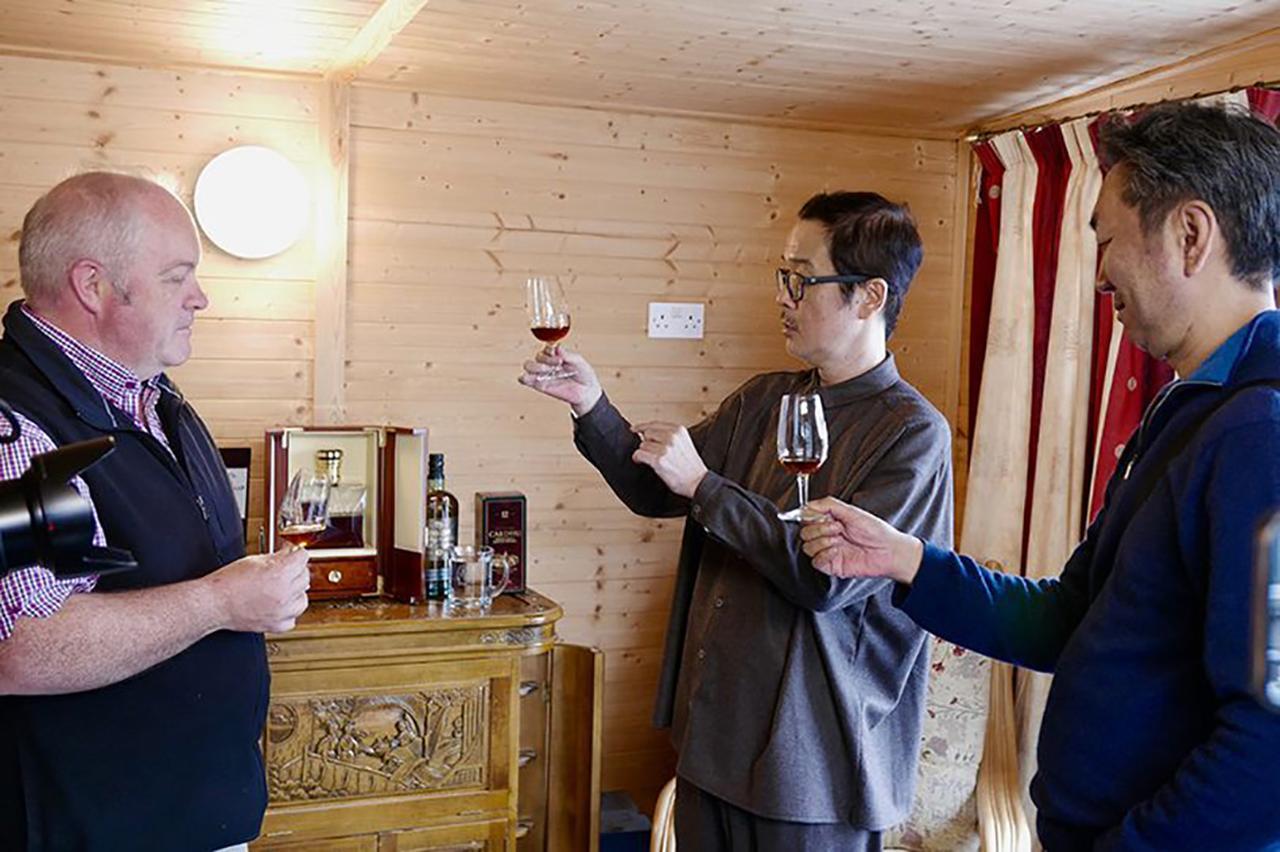 画像: ドライバー宅でジョニーウォーカーのスペシャルエディションをいただく。「スコットランドに来て一番美味しいお酒」と、リリーさん (C)2018, Condé Nast Japan & WOWOW Inc.