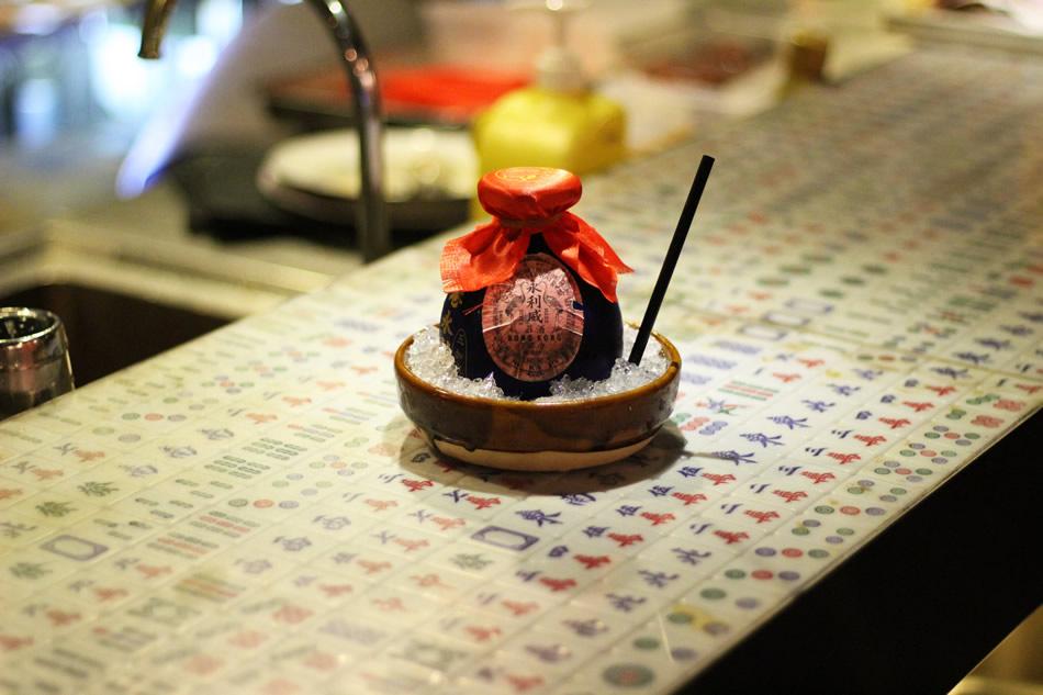 """画像: 五加皮酒をベースにした「""""Dong Ning Cha"""" 128」。古酒のカメのような器と、麻雀牌を敷き詰めたカウンターで、中華スタイルへのこだわりを感じさせる"""