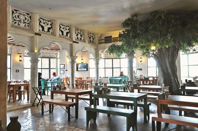 画像: 店内のいたるところに、伝統的な調度品や古き時代のドバイの白黒風景写真が飾られている