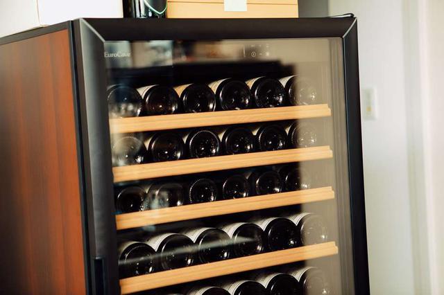 画像: 日本ソムリエ協会認定のワインアドバイザーの資格も持つ本田さん。事務所には大きなワインセラーが