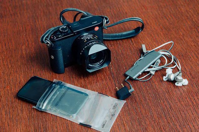 画像: 本田さん愛用の旅グッズ。左から、旅ラン用の防水・防塵カバーとスマートフォン、カメラ。いちばん右はノイズキャンセリング機能に優れ、機内で眠るときも心地よいイヤホン