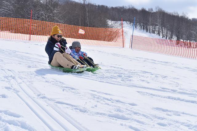 画像: 長女と旦那さんがスキーを滑っている間、長男とそりを楽しむ佐藤さん