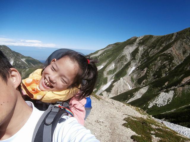 画像: 当時小学生だった娘さんを背負って山を登っている地引さん。お父さんの背中でとても楽しそうに笑っている