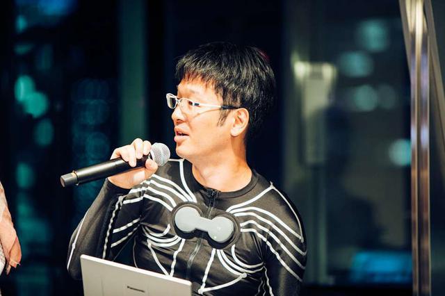 画像: 株式会社Xenomaの網盛一郎さん。自社で開発した、筋肉の動きを測るセンサーが衣服に一体化したスマートアパレル「e-skin」を着用中