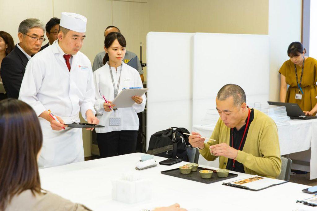 画像: 試食する石川さんを緊張した面持ちで見つめる、JRCのファーストクラス調理担当・西浦嘉明シェフ