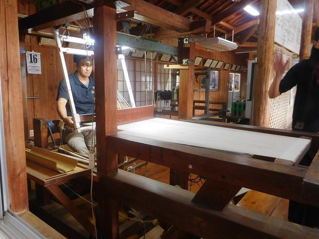 画像: 機織り機にズレないように糸をセットするのも大変な作業。真剣な表情が素敵です。