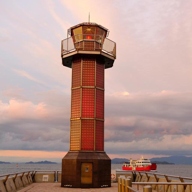 画像1: 宵闇が迫る中、灯台全体が赤く光り始めます。ピンクに染まる景色と灯台、行き交うフェリーの姿は感動的な光景でした。