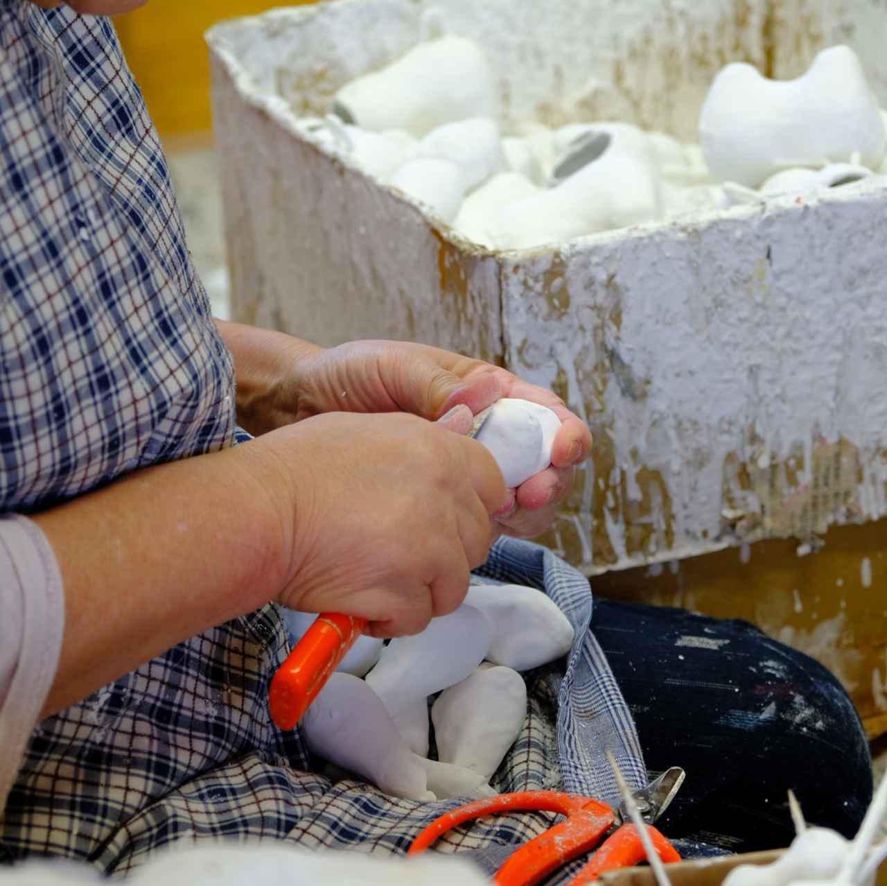 画像: 和紙を重ね、乾かしたら型から外し、胡粉を塗ります。滑らかになるよう削り落とす、丁寧な手作業です。