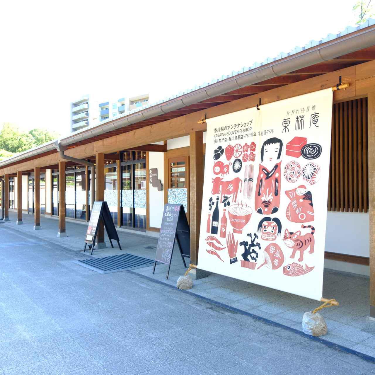 画像: 大きなのれんがかかる「かがわ物産館 栗林庵」。こののれんは、香川の伝統的工芸品「讃岐のり染」で描かれています。