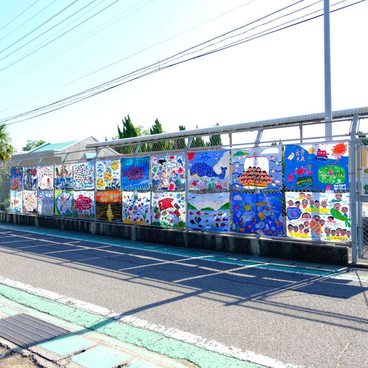 画像: 島内を周る間に通る保育所、小学校、中学校には手作りの絵画やアートが飾られています。可愛くも微笑ましいお出迎えを受けました。