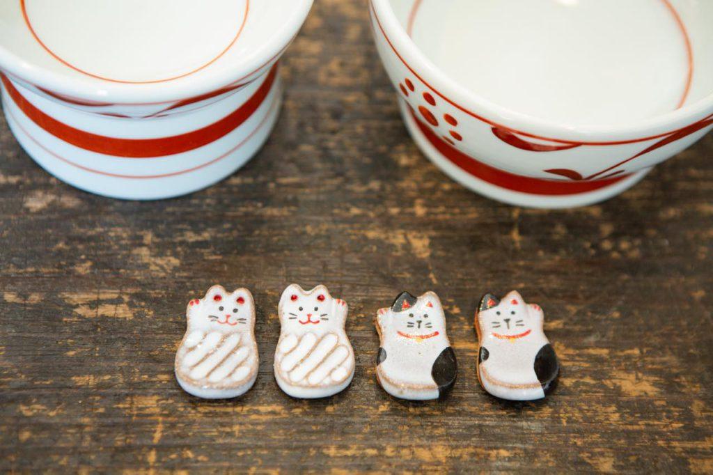画像: 招き猫の箸置きは、右前足と左前足それぞれを上げている2種類の猫で計4種類。後ろの器はもうひとつの人気商品で、砥部焼のペット専用フード入れ(左)とお水入れ(右)。