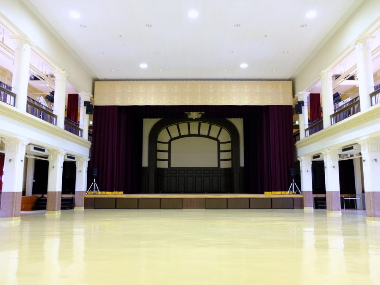 画像: 内部は舞台とホール、そして2階バルコニー。当初は日本海軍の催しなどに利用され、その後米軍接収時代はダンスホールなどとして使われました。そして今では、演奏や演劇、ダンスの発表会などで利用されるホールとなっています。