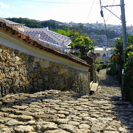 画像: 首里金城町石畳道を下って行きます。遠くには近代的な街が見えて不思議な感じです。