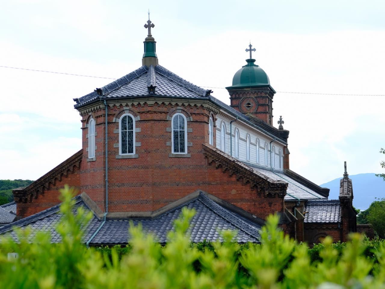 画像: 裏側から見た雰囲気も、これがまた全然違っていて、八角形のドーム、そして黒光りする瓦屋根と印象的。様々な教会に携わってきた鉄川が自らの建築の技を全て結集させ完成させたと言っても過言ではない、素晴らしい教会です。