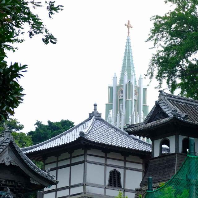 """画像: 寺院脇の坂道のどの角度からも見ることが出来る、""""ならでは""""の景色。現在は修復中でしたが寺院屋根のその先に教会の塔が見えるという風景は長崎らしく、一見の価値ありです。"""