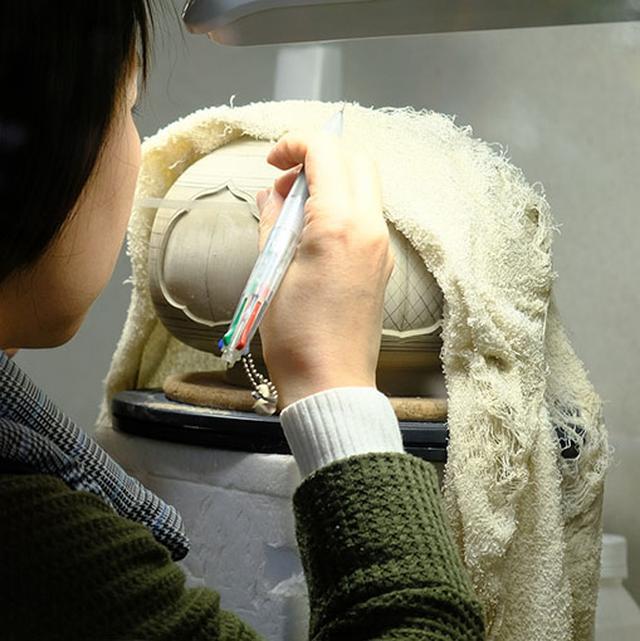 画像: 白薩摩に彫りを施す作業。濡れたタオルで水分を調整しながらの作業。絵付けだけでなく彫りによる凹凸やデザインをすることでより優美で豪華、気品あふれる調度品へと仕上がります。