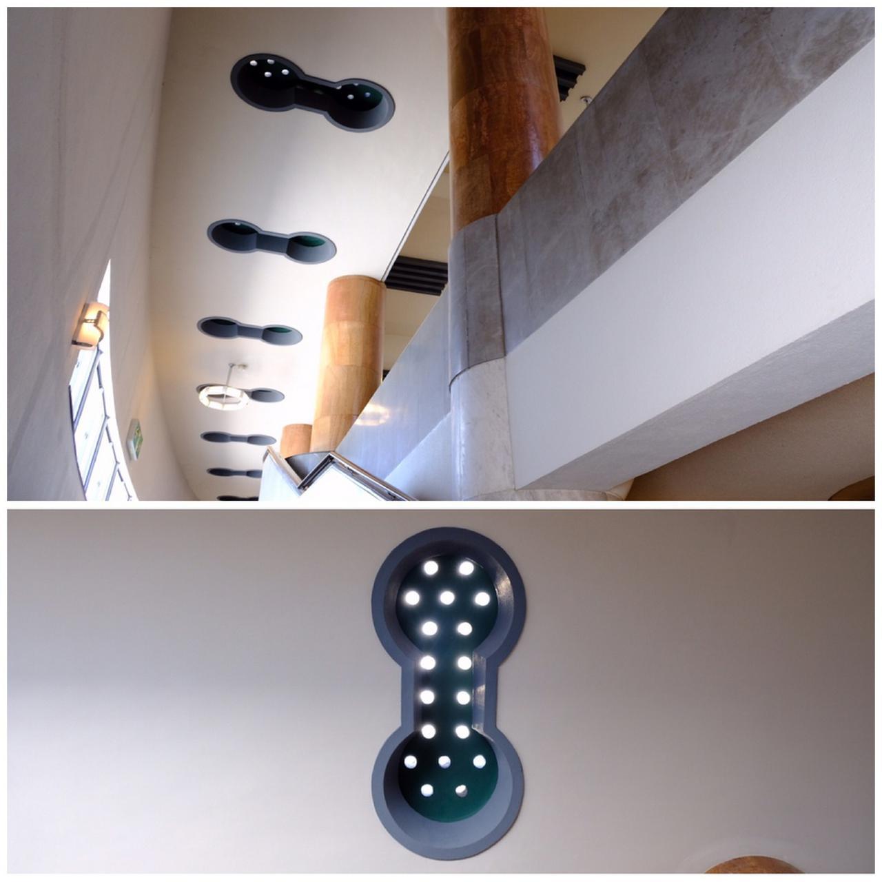 画像: 2階への階段天井にはバーベルのような形の明かり取り。建物中央が長く、端になるほど天井幅と共に短くなっており、空間を広く見せる造りとなっています。