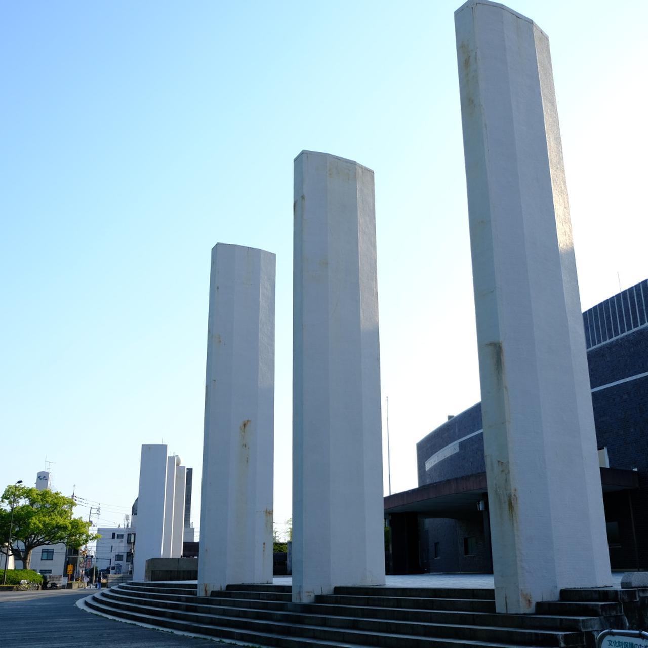 画像: まず外観。左右に3本ずつ並んだ塔とその中央に置かれた記念碑は、渡辺が関わった7つの会社を表しています。