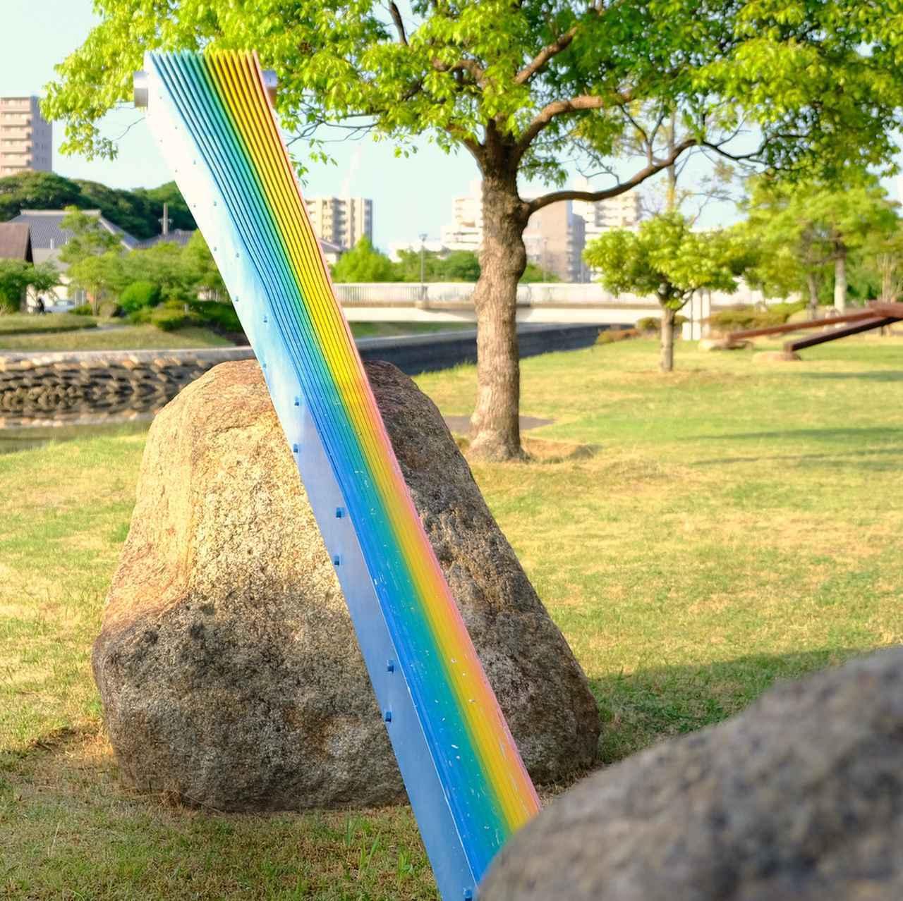 画像: 人工的な素材に「虹」という自然界の色が着色され、さらにそれを自然石が支えている。自然と人工という相対するものがひとつの作品になるという、私たちの生きる世界の縮図なのかなと解釈しました。