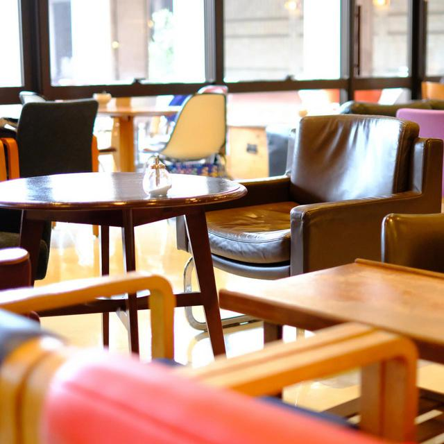 画像: カラフルな椅子がランダムに並べられた店内。おしゃれな空間で、窓からさす光で明るい雰囲気です。