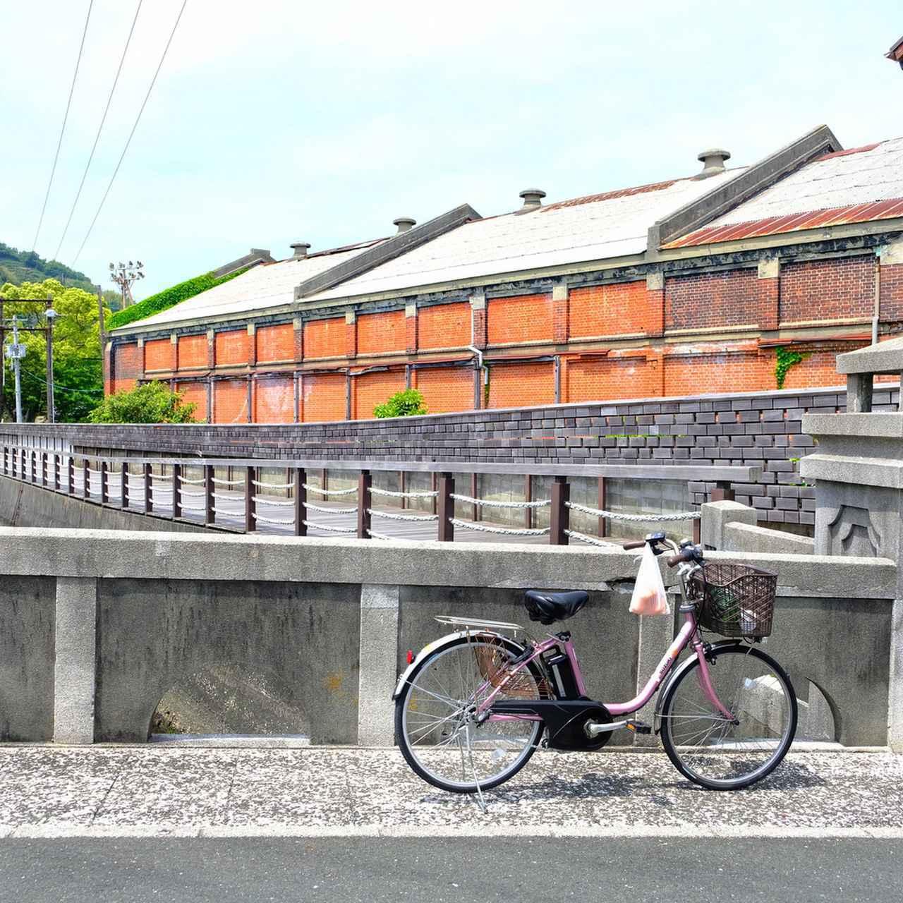 画像: 街の中を流れる宮内川とそれにかかる美名瀬橋。その向こうには旧東洋紡の赤レンガ倉庫。