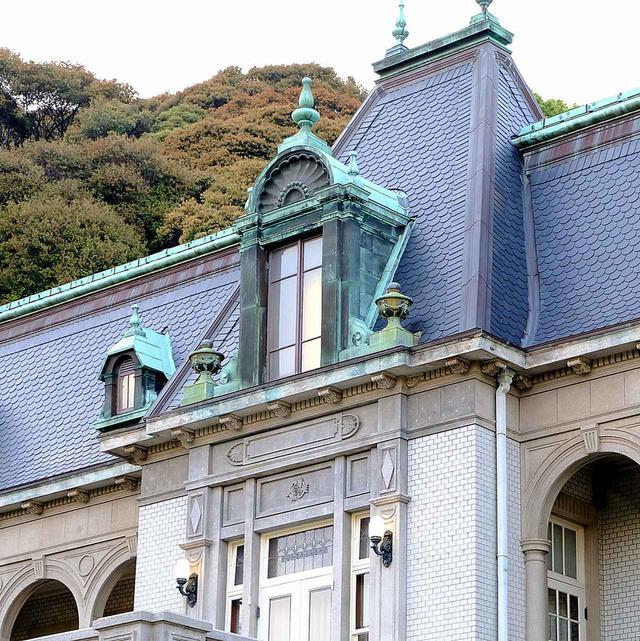 画像: 屋根は丸くうろこのように張られたスレート、銅板の出窓、外壁にはタイルが使われています。