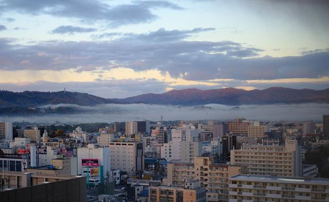 画像: 早起きしたらこんな景色が見られました。朝日に染まる山々と、街に広がる雲海。