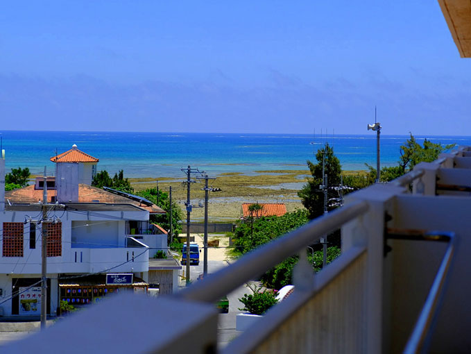 画像: 海外みたい!広めのベランダはお隣とつながっていて丸見えです。遠くにイーフビーチが見えました!あぁ空が広い。
