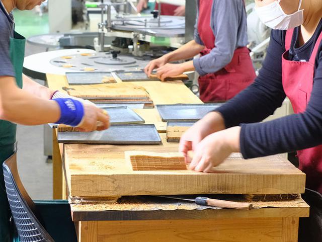 画像: 機械で焼かれた生地はできたてではまだ柔らか。それを手早く包丁でカットし、並べたら乾燥させます。熟練の技を活かしたひとつひとつの工程を経て、伝統菓子が作られていきます。