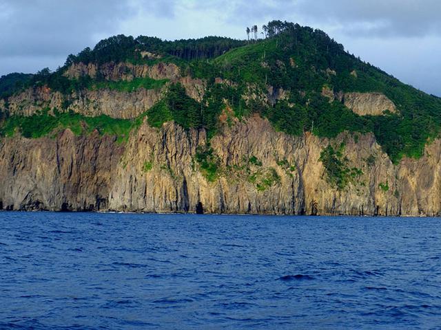 画像: 海から見る隠岐の島もいいものです。縦の筋になっているのは火山噴火で生まれた「柱状節理」。ローソク島もこの一部からでき上がったものです。