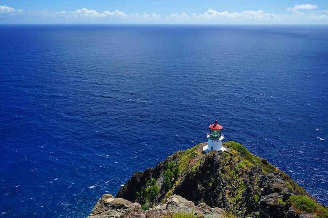 画像: 白壁と赤い屋根の灯台が紺碧の海に映えます