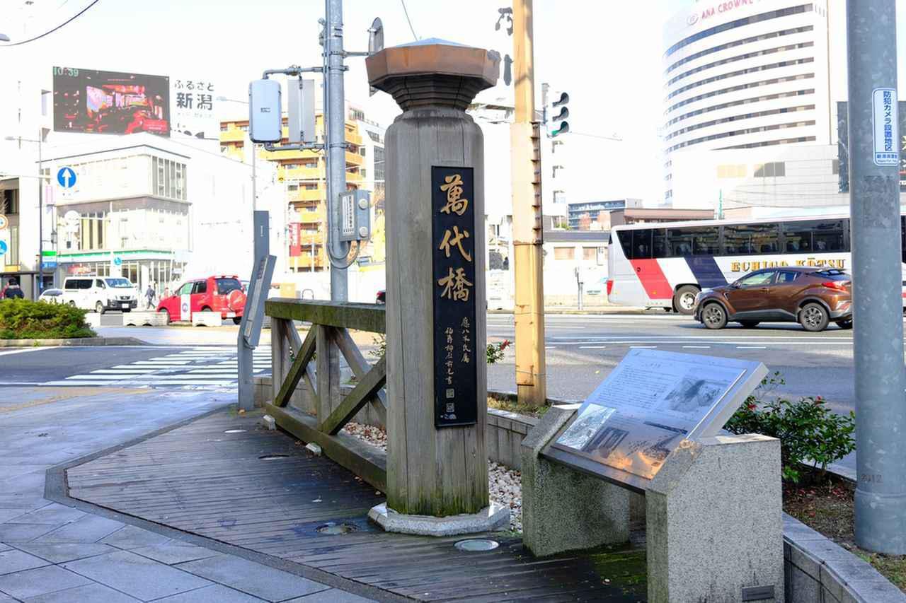 画像: 萬代橋よりもずっと手前(駅方面)にかつての萬代橋の親柱が立っていました。昔の萬代橋は今よりも長く川幅も広かったため、かつては親柱が立っているところから橋が始まっていたそうです。