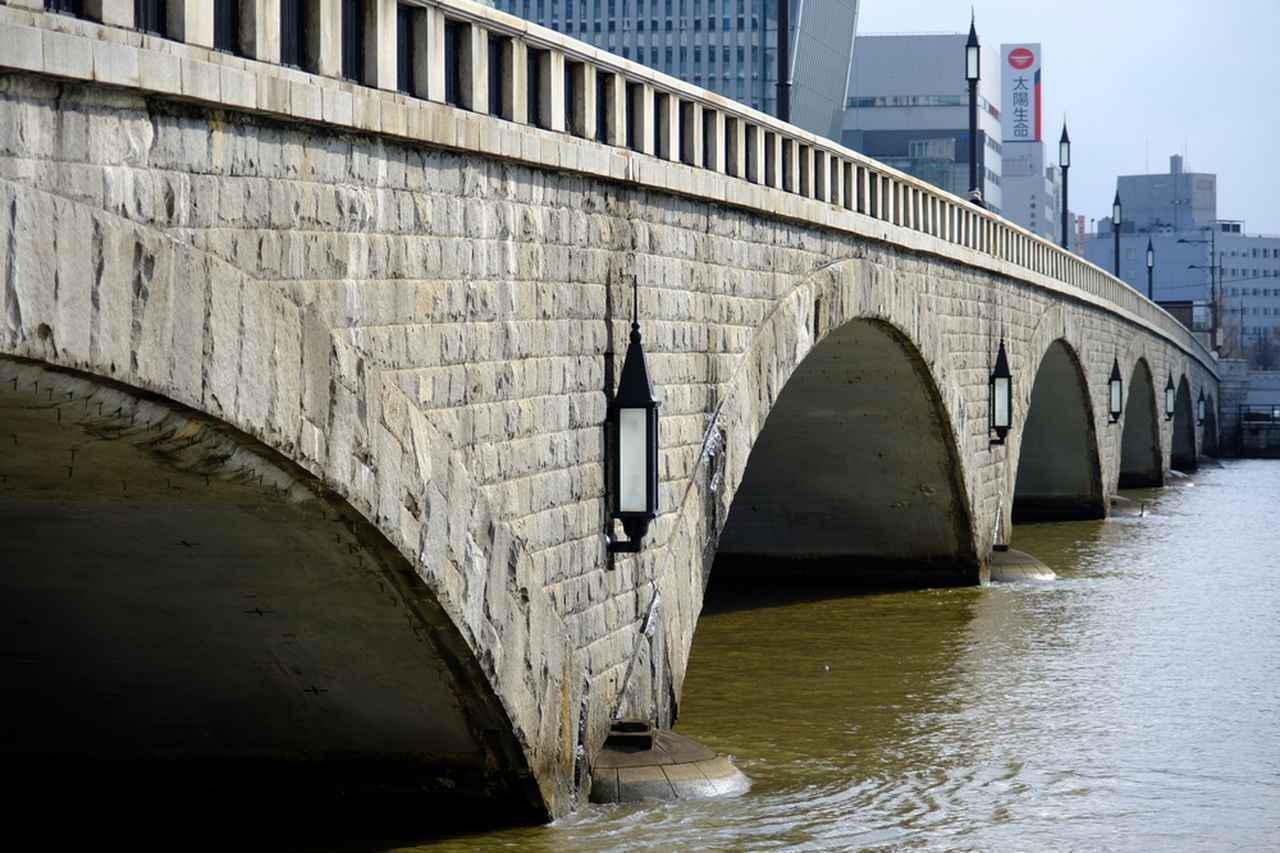 画像: 信濃川にかかる6連アーチの美しい橋です。川沿いには「やすらぎ堤」遊歩道が整備されており、橋の構造やデザイン、橋全体に施された花崗岩などをじっくり下から眺めることもできます。
