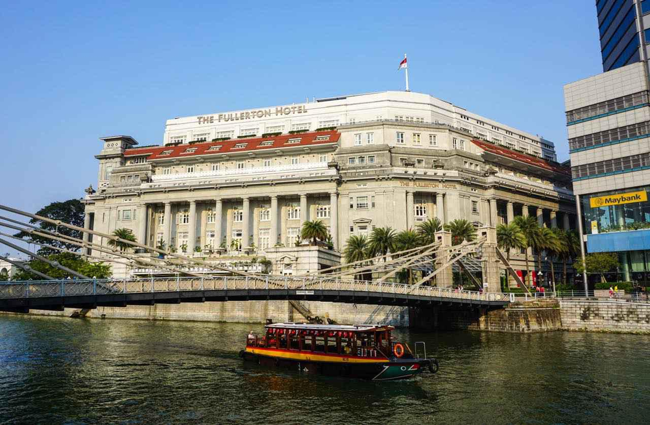 画像: 白壁が堂々とした印象のザ・フラートン・ホテル前を通過 Phuong D. Nguyen / Shutterstock.com