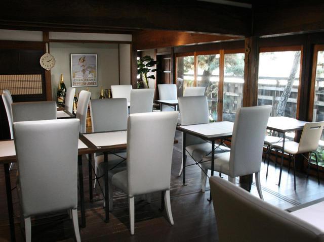 画像: 白を基調としたテーブル&チェアーが並ぶ。ガラス貼りの扉で、自然との一体化も