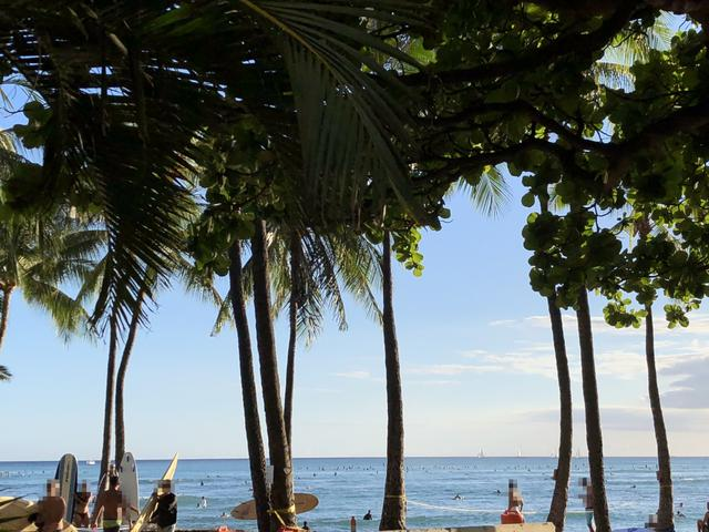 画像: 海を楽しむ人で賑わうワイキキビーチ。奥に一列に見えるのは波を待つサーファー達です。