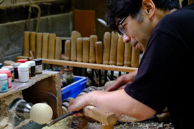 画像: 平賀雅幸さんの作業の様子。足でろくろの回転を操作しながら手元の工具で削りだしていきます。