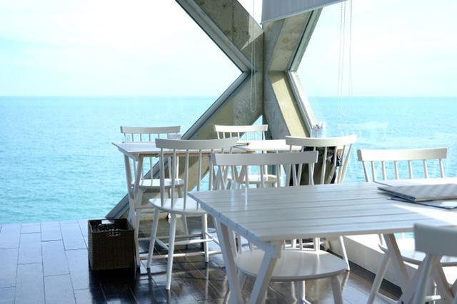 画像: ガラス張りのカフェは海に突き出るように建てられており、窓からは海岸が遠くまで見渡せます。2階の窓際の席に座ります。
